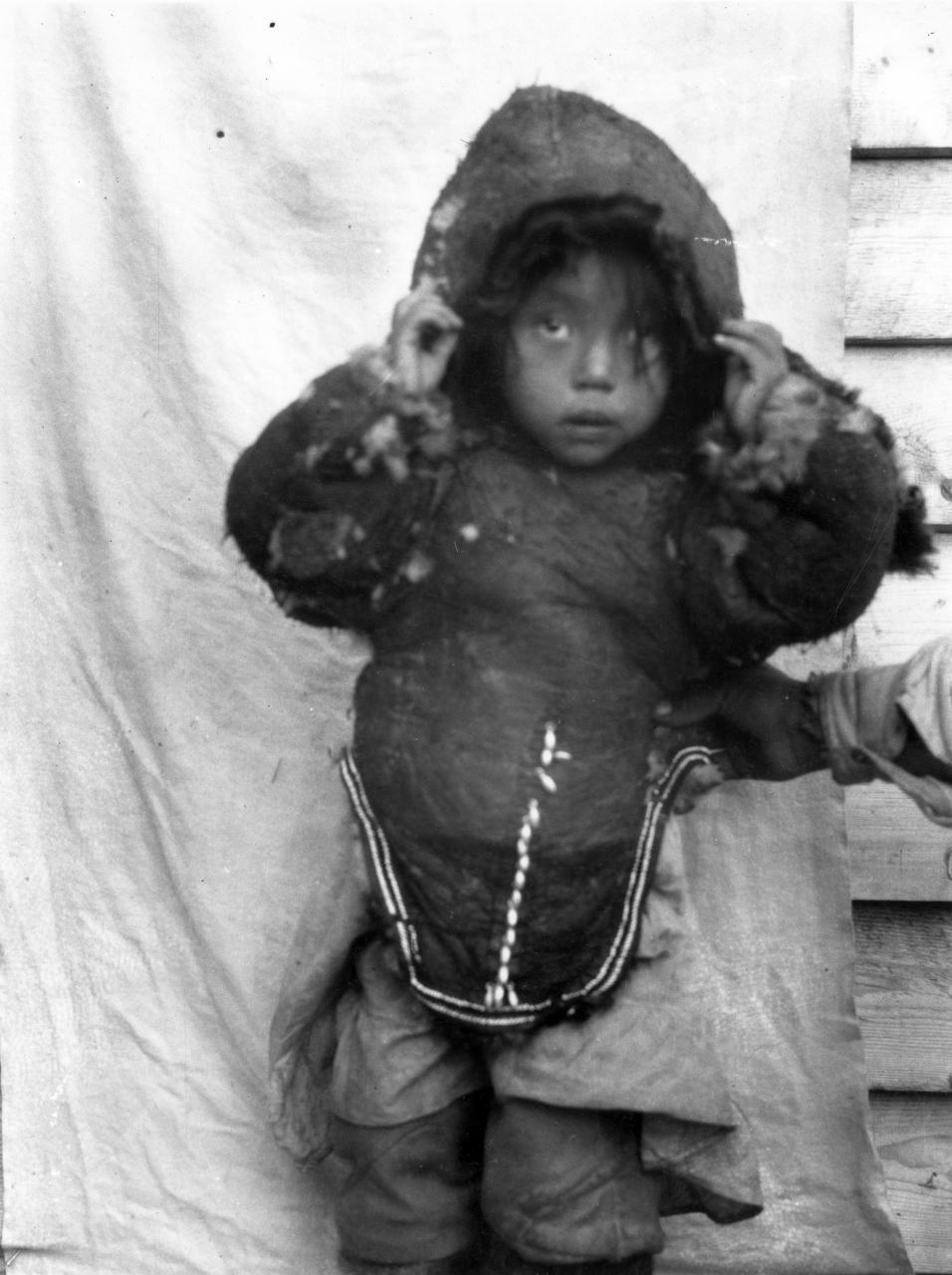 Black and white photo of a child wearing an eider skin parka.