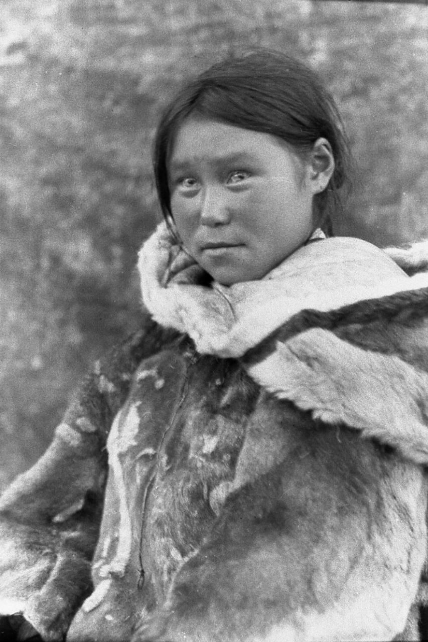 Black and white picture of a woman wearing a caribou skin parka.