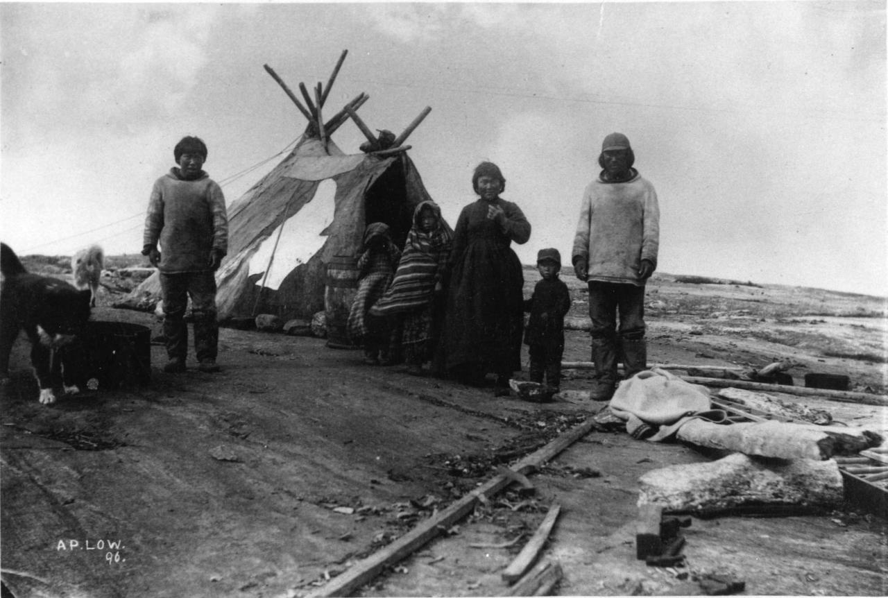 Black and white picture of an Inuit family and a dog in front of a skin tent.
