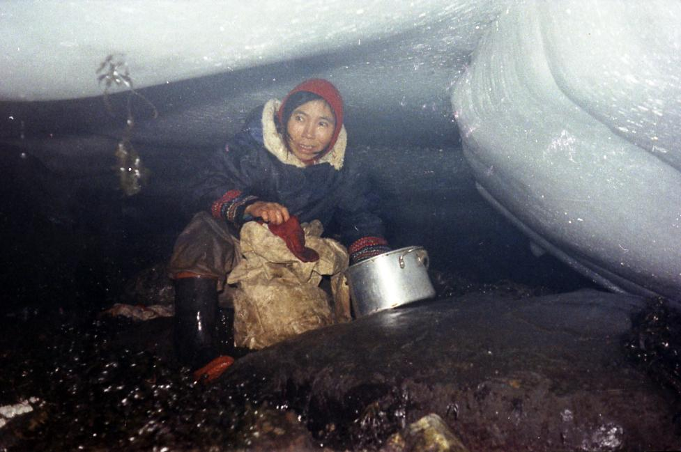 Color photo of a woman who is squatting under an ice surface. Before her, we see a metal pot and a paper bag. She wears rubber boots.