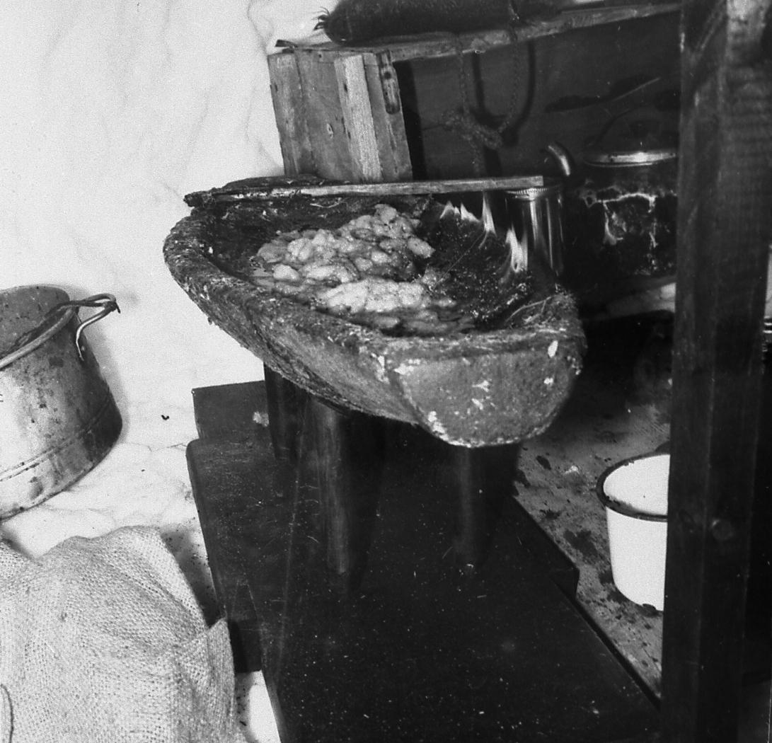 Black and white photo where we see a qulliq lit with a stick resting on the edge. Near the qulliq you can see a wooden box and a metal pot.