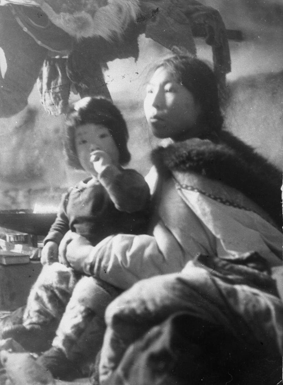 Photo in black and white of a woman and her son. The child is seated on his mother, he seems to suck his thumb. The woman is wearing a amauti. They seem to be in an igloo.
