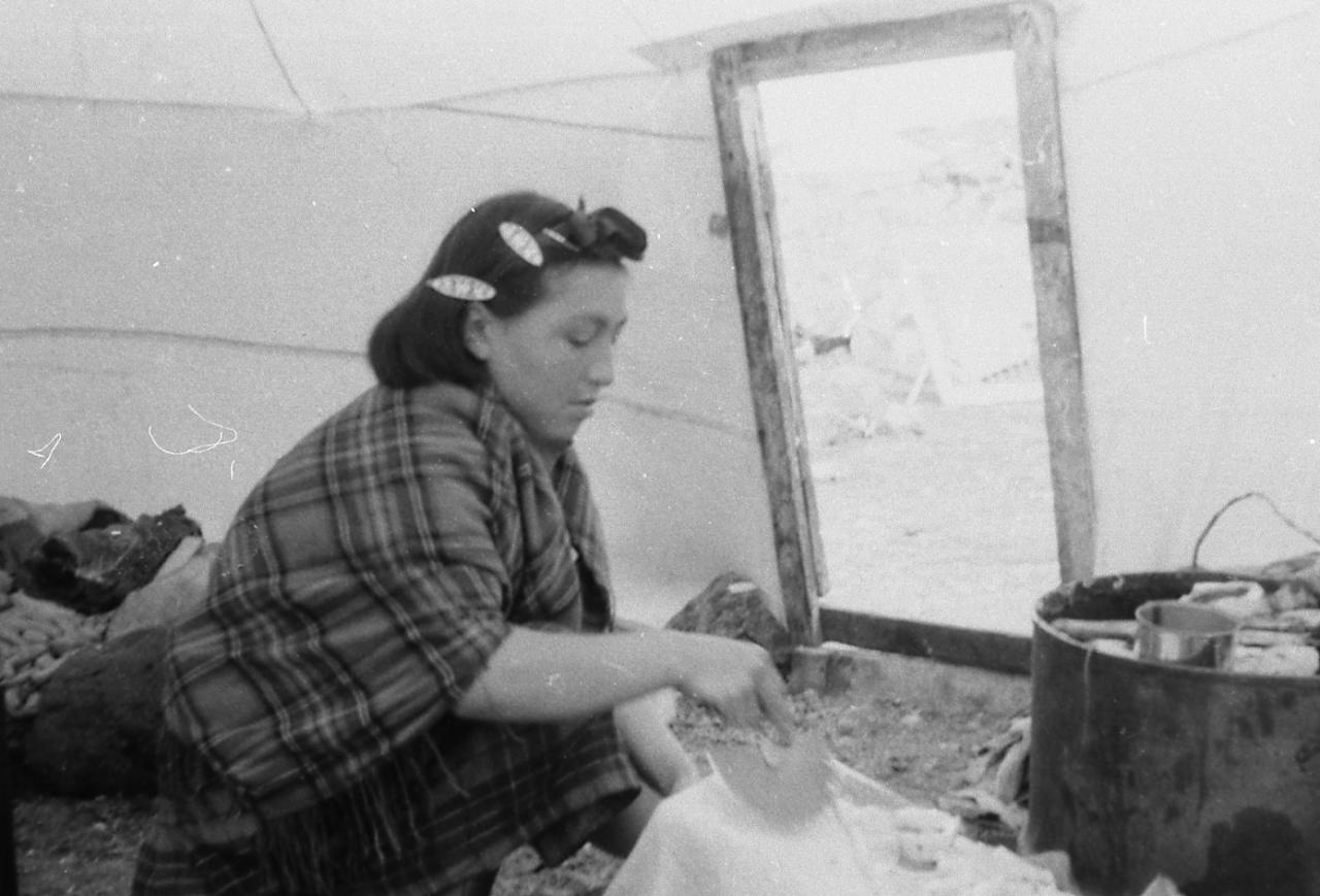 Black and white photo of a woman. It is a side view of her, she is inside a skin tent and works with an ulu.