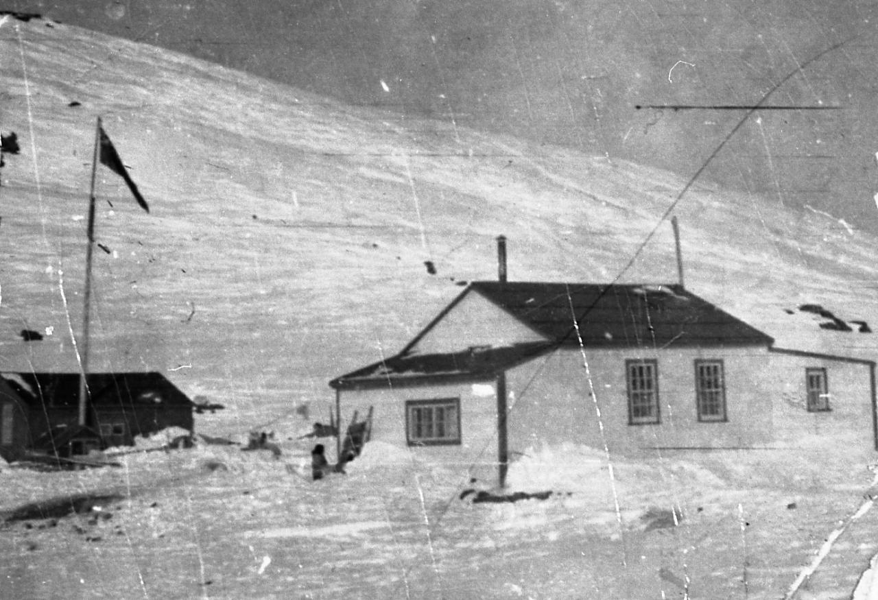 Black and white photo of a white house and a shed -  on top of which we see a flag - on the side of a snowy hill.