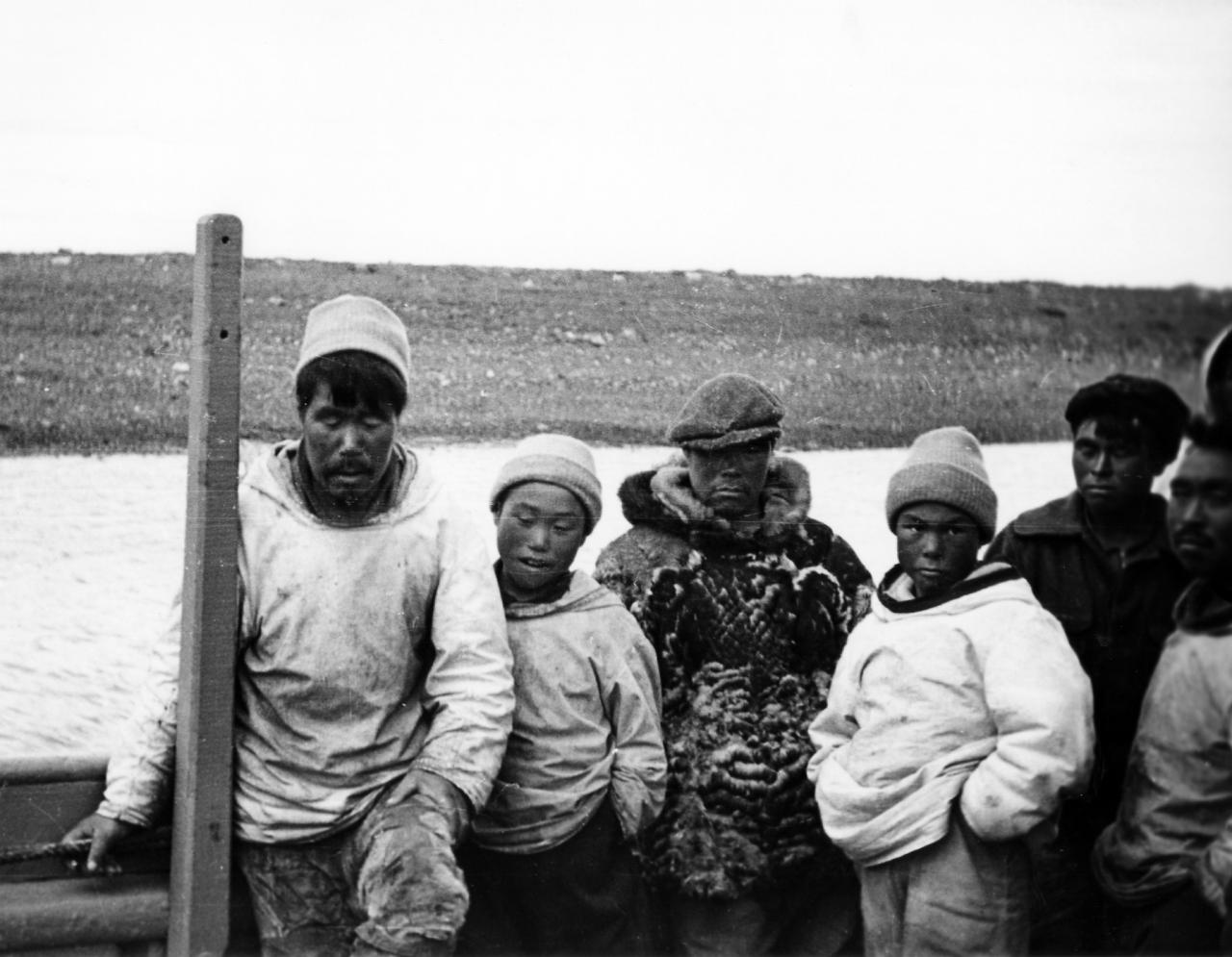 Black and white picture of six Inuit who seem to be waiting. They are outside, leaning against a handrail.