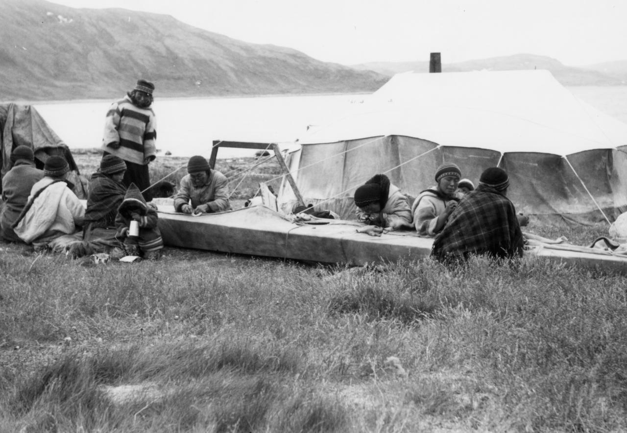 Black and white picture of women sewing a kayak. A child is near them. In the background you can see a large tent, a lake and a mountain.
