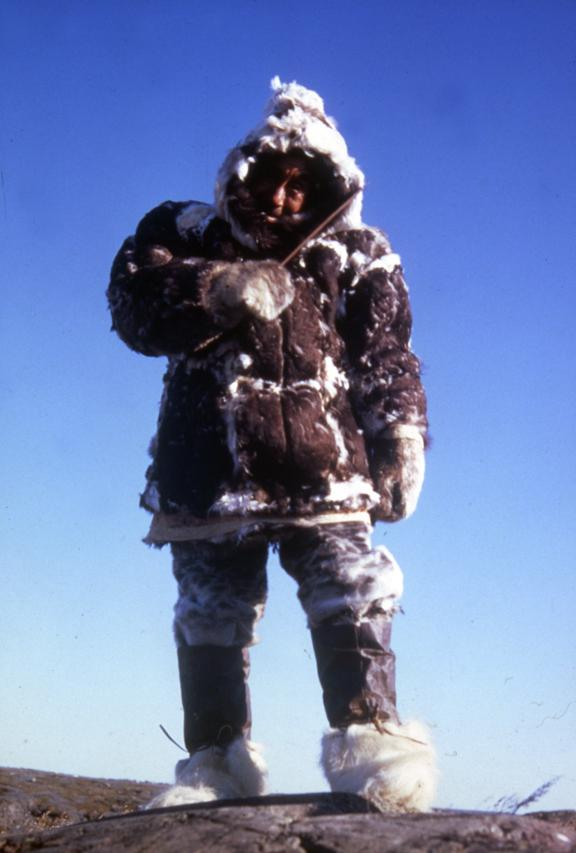Picture of a man facing the camera. He is wearing an eider skin parka.