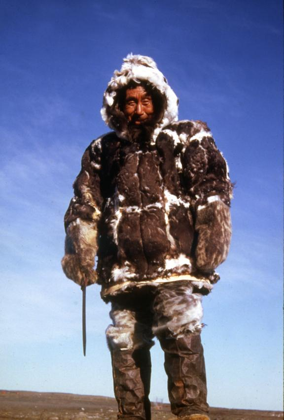 Picture of a man wearing an eider skin parka. He is turning his back to the camera.