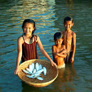 Children bathing with a basketful of fish. Photo © Zeb HOGAN / WWF-Canon