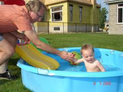 Félix glisse dans la piscine avec l'aide de  son grand-papa.