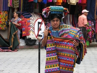 Mayan people today keep the tradition of weaving beautiful bright textiles, like this lady in Guatemala
