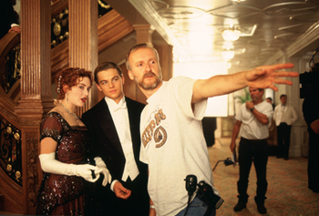 Kate Winslet (as Rose DeWitt Bukater) and Leonardo DiCaprio (as Jack Dawson) discuss a scene with Writer/Director/Producer/Editor James Cameron in TITANIC