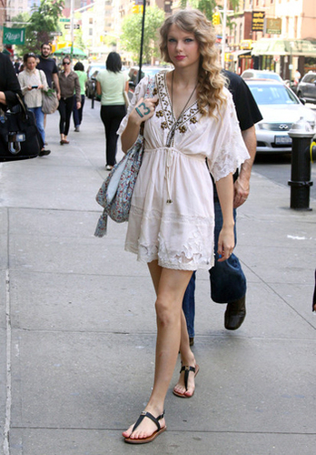 Taylor Swift pairs a flirty white dress with cool flat sandals