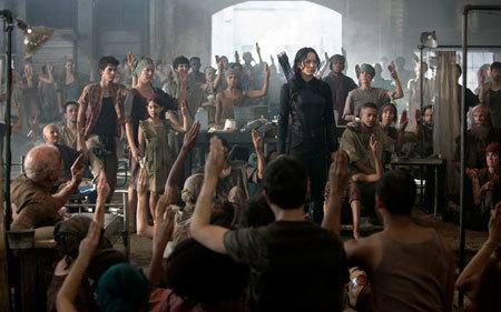 A crowd salutes the Mockingjay