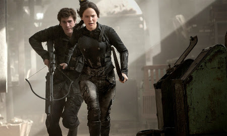 Katniss and Gale (Liam Hemsworth) run from Snow's bombers