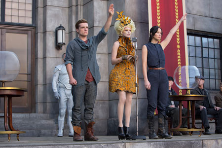 Peeta and Katniss (with Effie) give the rebellion salute