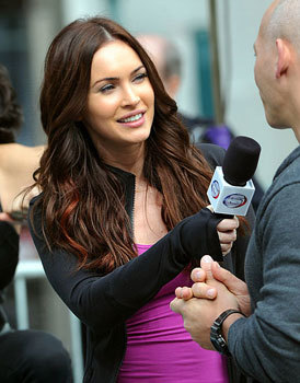 April (Megan Fox) doing an interview