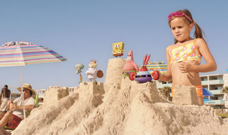A little girl wonders what has invaded her sand castle