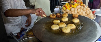 Delicious aloo tikki frying at a vendor's stall in India.