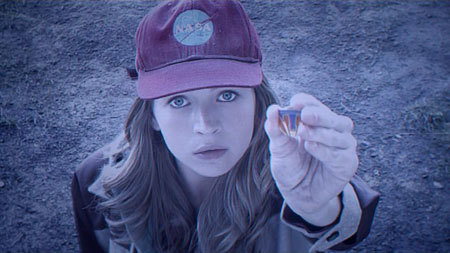 Casey (Britt Robertson) holds the transporter pin