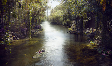 Mowgli floating down the river on Baloo