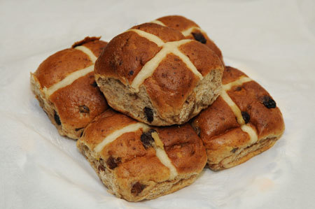 A hot cross bun is a spiced sweet bun made with currants or raisins and marked with a cross on the top