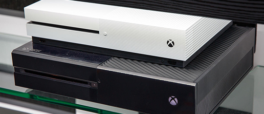The Xbox One S sitting on top of the original Xbox One.