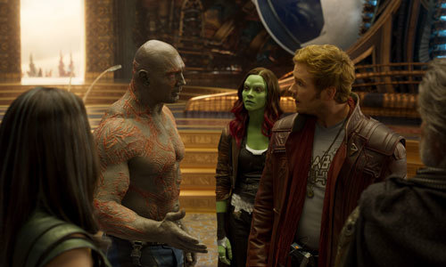 Gamora (Zoe) looks on as Drax talks to Star Lord