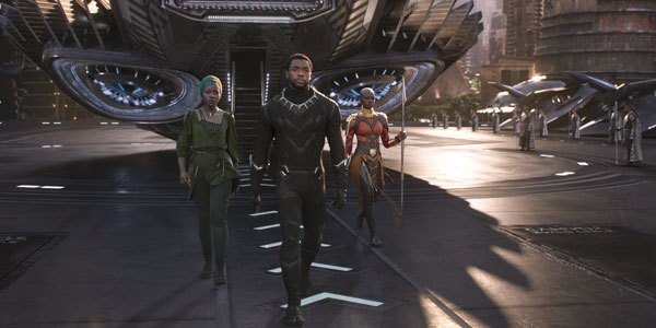 Black Panther flanked by Nakia and Okoye, enters the city