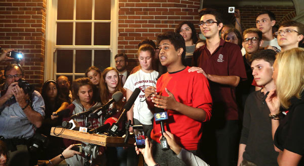 Tanzil Philip, a student survivor addresses the crowd surrounded by fellow classmates