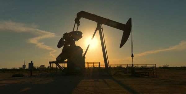 Industrial oil pump jack pumping crude oil for fossil fuel energy with drilling rig in oil field