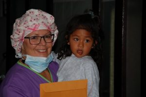 Nurse with cute scrub hat helping little girl