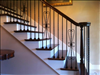 Reclaimed Longleaf Pine Stair Treads blend beautifully with wrought iron railings.
