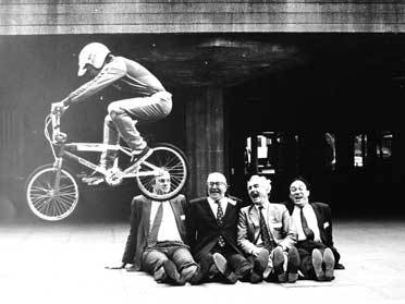 A BMX rider jumps over a group of dignitaries