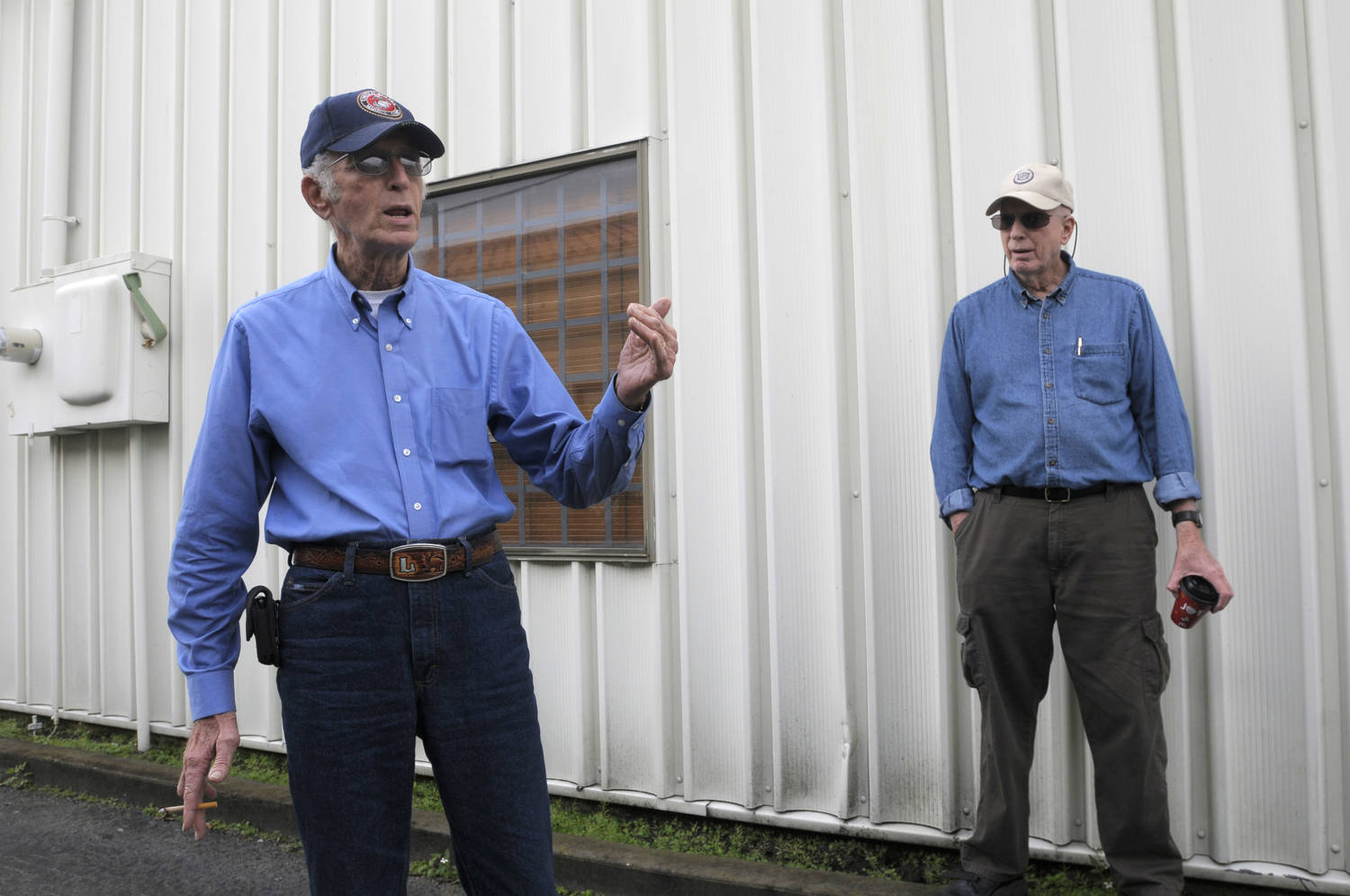 Two men, both wearing blue work shirt and baseball caps, stand near a steel building. The man on the left is speaking, the other looks at him from slightly farther away.