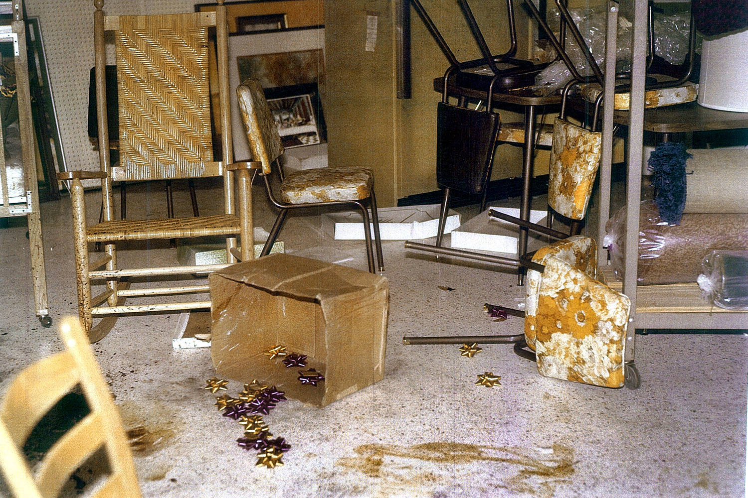 Police evidence photograph of furniture, gift wrapping bows, and blood stains scattered on the floor.