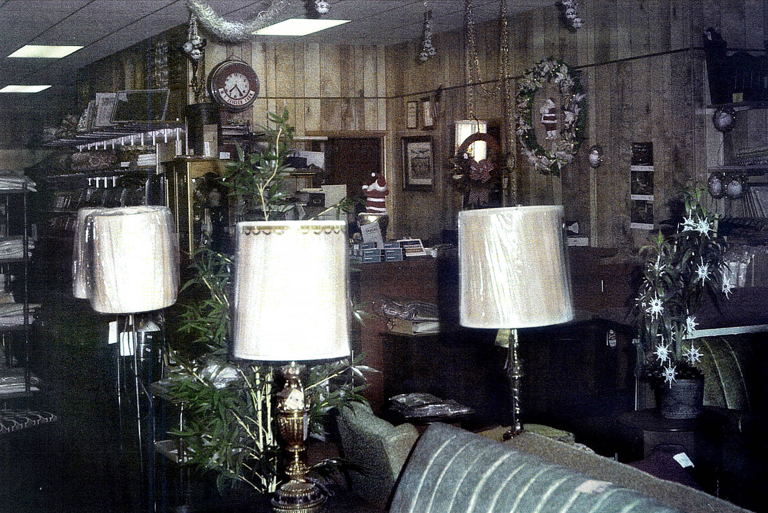 A police photograph of the store. Lamps, wrapped in plastic, in the foreground. On the wood-paneled wall in the background can be seen Christmas decorations and a clock stopped at 7:24.