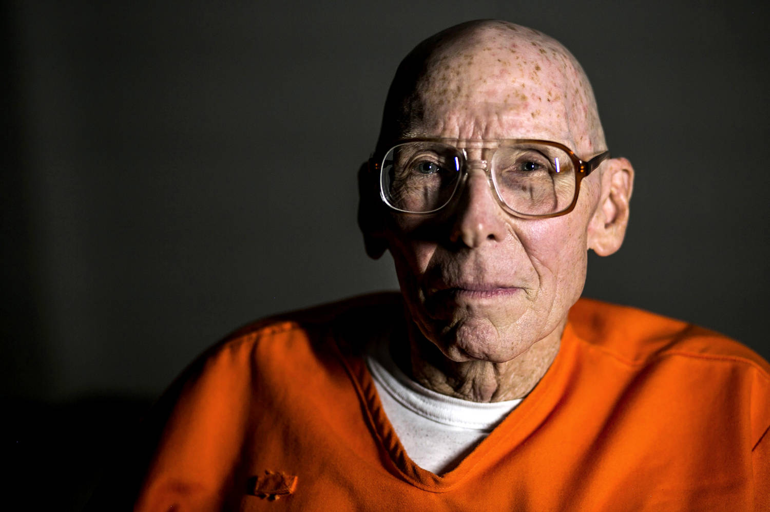 A very old man, either bald or with a very short haircut. He is wearing glasses and an orange prison jumpsuit. He is looking directly into the camera.