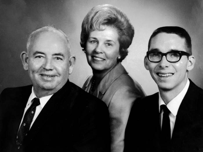 A family poses for a portrait, father on the left, son on the right, and mother behind and between them.
