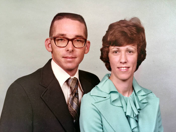 Studio photograph of a couple. The man is wearing glasses, a suit and tie, the woman wears a nice blouse and jacket.