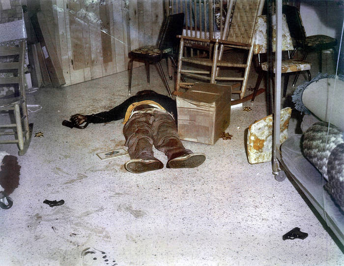 Police evidence photograph of a dead man with two guns nearby