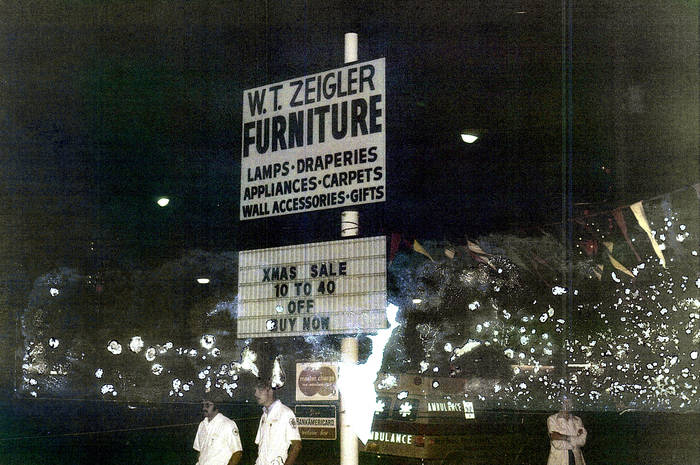 A badly-aged photographs of the furniture store sign at night. Below the sign are an ambulance and emergency medical technicians.