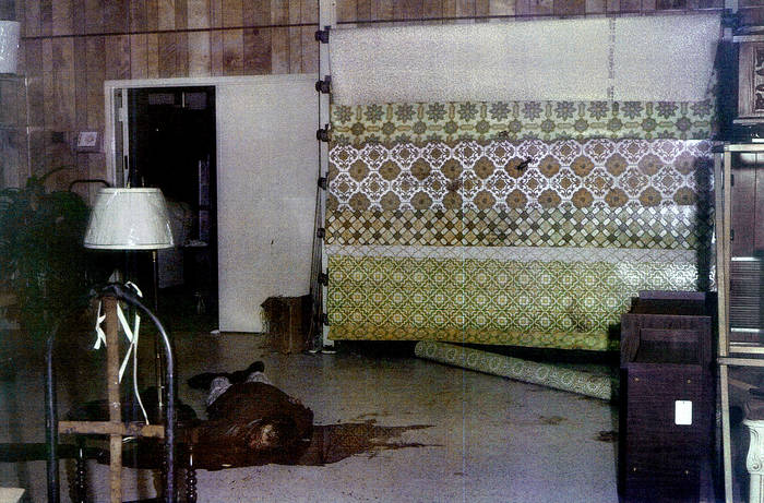 Police evidence photograph of a dead man with linoleum flooring rolls in the background