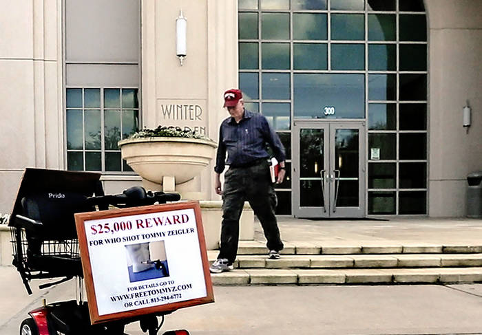 A man in a baseball cap, carrying a book under one arm, walks out of a building toward his mobility scooter parked on the sidewalk. The scooter has a sign offering $25,000 reward.