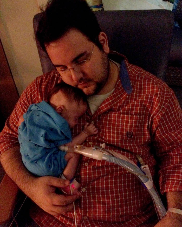 A sleepy dad holds his baby against his chin and nods.