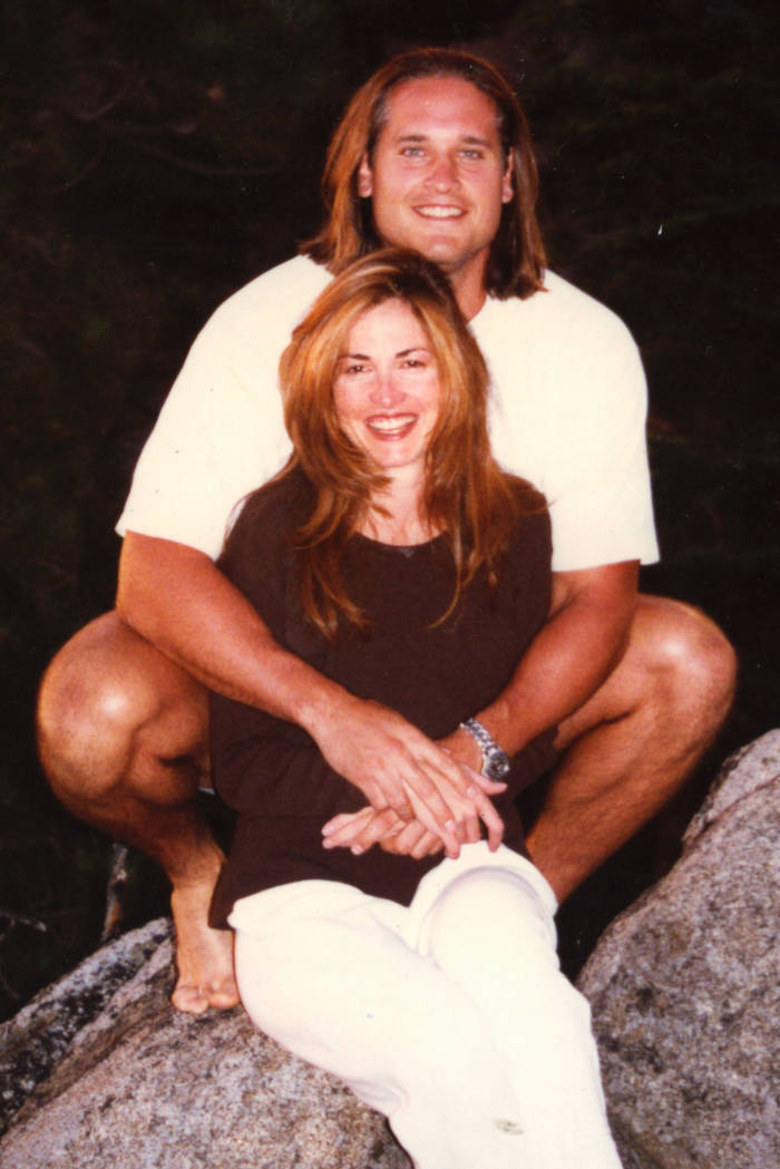 A young couple sitting on a rock and smiling.