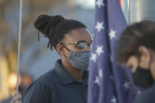 A woman recruit stands next to a US flag.