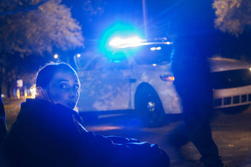 At night, a seated woman looks over her shoulder towards the camera, a police car with blue lights on in the background.