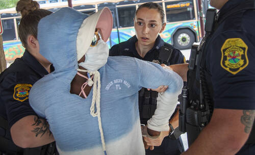 Three officers detain a woman wearing a hoodie and sunglasses, holding her arms behind her.