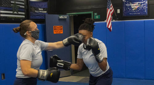 One woman lands a punch on another woman's face, wearing boxing gloves.